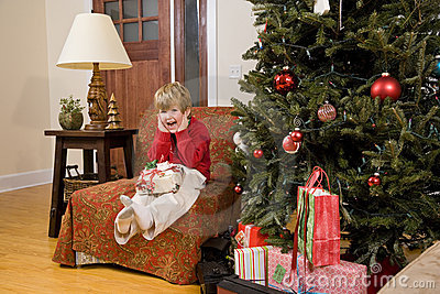 Excited little boy with present by Christmas tree