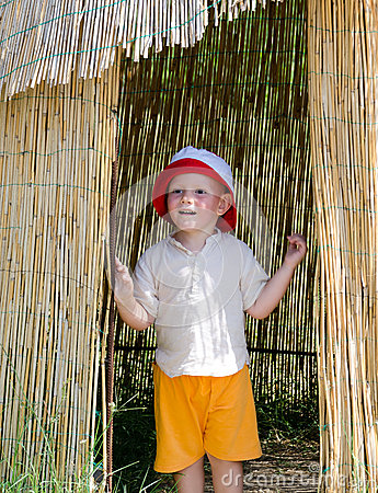Excited little boy in a reed hut