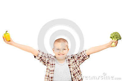 An excited little kid holding broccoli, and a pepper in his hand