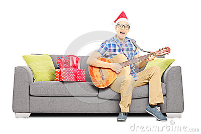 Excited male with christmas hat sitting on a sofa and playing a