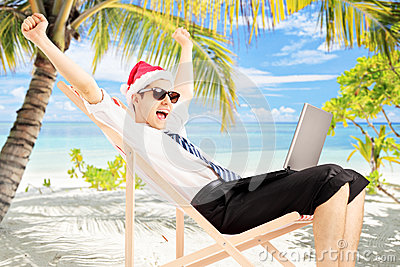 Excited male with santa hat sitting on a chair and working on a