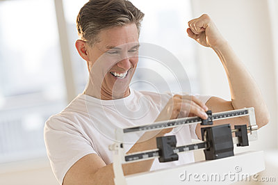 Excited Man Clenching Fist While Using Weight Scale