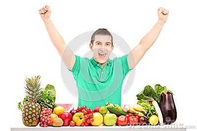 Excited man raising hands and posing with a pile of fruit