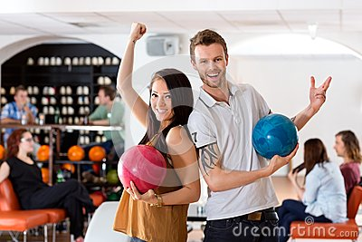Excited Man And Woman Holding Bowling Balls