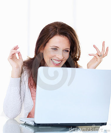 Excited middle aged woman looking at laptop