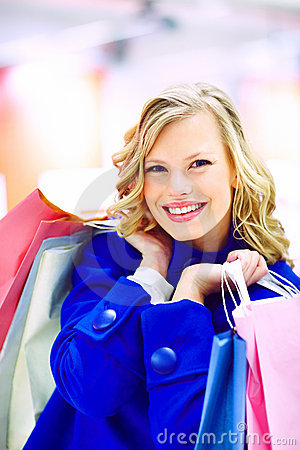 An excited pretty woman holding shopping bags