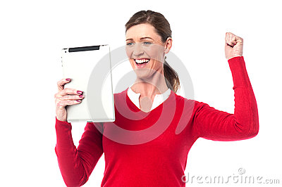 Excited pretty woman holding touch pad