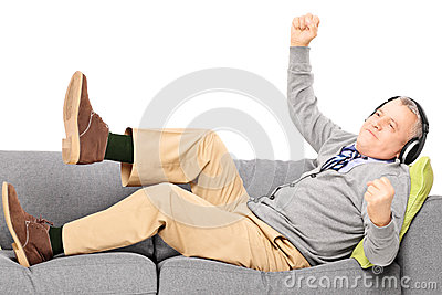 Excited senior male seated on a modern couch listening music