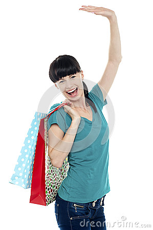 Excited shopaholic woman carrying bags