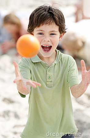 Excited small boy playing with a ball