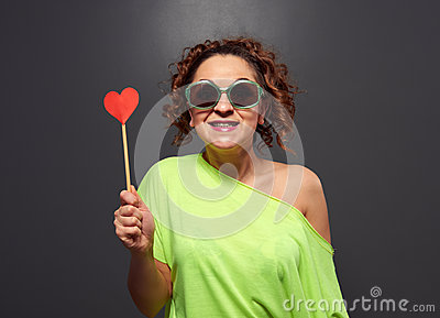 Excited smiley girl holding small red heart