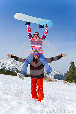Excited snowboarder with girl on his shoulders