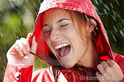 Excited teenage girl enjoying rain outdoors