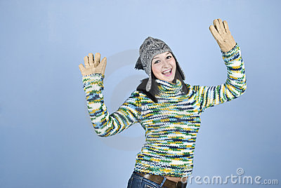 Excited winter girl with arms raised
