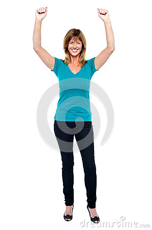 Excited woman in celebration mood with raised arms