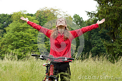 Excited woman cyclist with hands outstretched