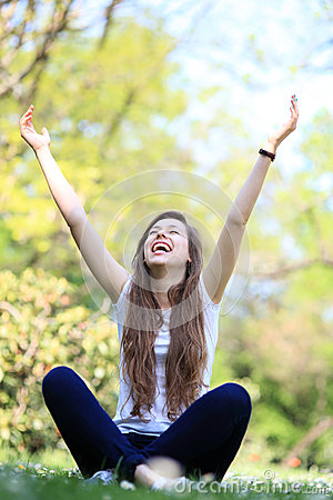 Excited woman sitting with arms raised