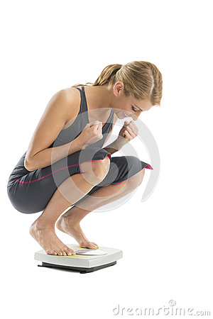 Excited Woman Weighing Herself On Weight Scale