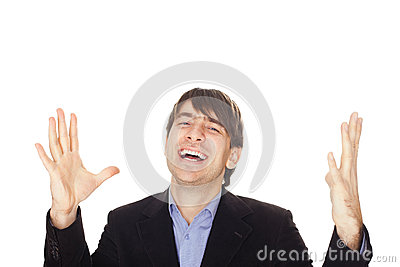 Excited young business man with arms raised in success
