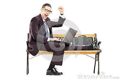Excited young businessman with a laptop sitting on a bench