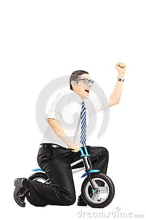 Excited young businessperson riding a small bicycle and gesturin