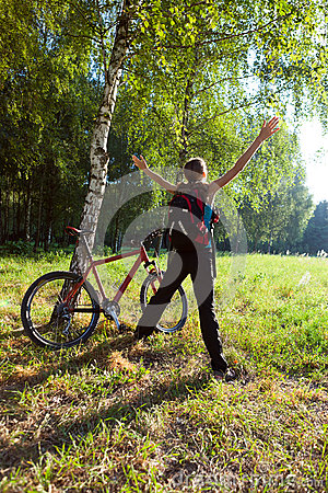 Excited young cyclist standing in a spring park