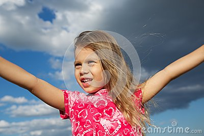 Excited Young Girl against Cloudy Sky