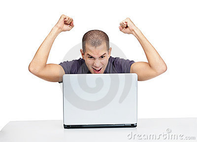 Excited young guy looking at laptop