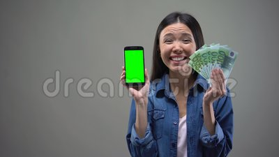 Excited young lady holding smartphone and euro banknotes, online lottery winner. Stock footage stock footage