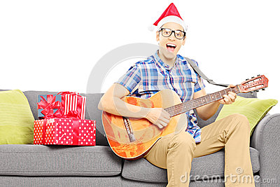 Excited young male with christmas hat seated on sofa playing an