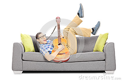Excited young male lying on a sofa and playing a guitar