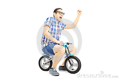 Excited young male riding a small bicycle and gesturing happines