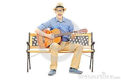 Excited young man playing acoustic guitar seated on a bench