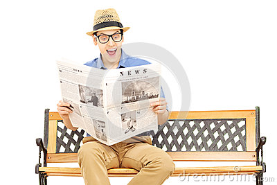 Excited young man reading a newspaper seated on bench