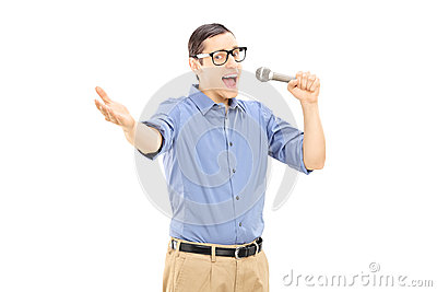 Excited young man singing on microphone