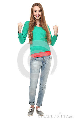 Excited young woman clenching fists