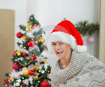 Excited young woman near Christmas tree