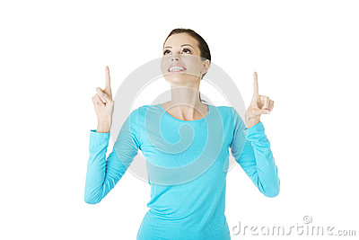 Excited young woman pointing on copy space