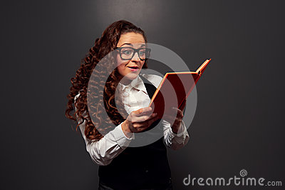 Excited young woman reading the book