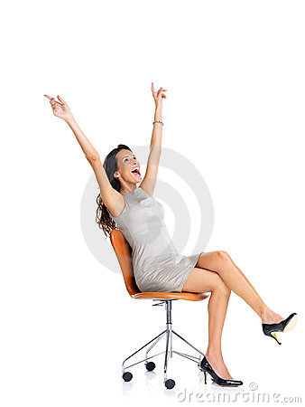 Excited young woman sitting on chair celebrating