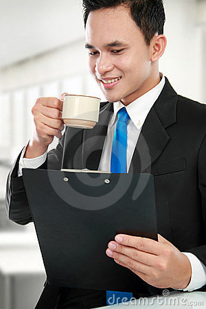 Executive reading a report while drinking