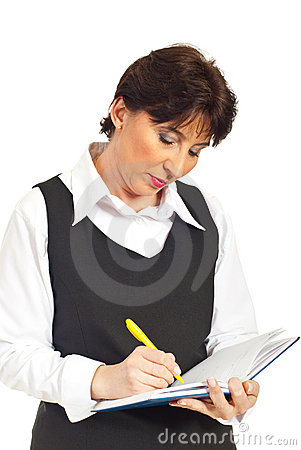 Executive serious woman writing in agenda