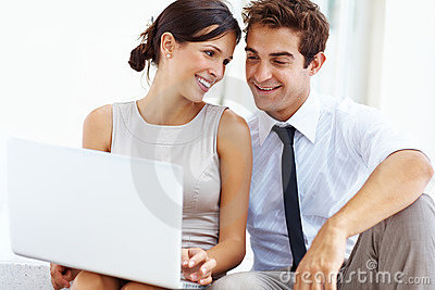 Executive sitting with his girlfriend using laptop