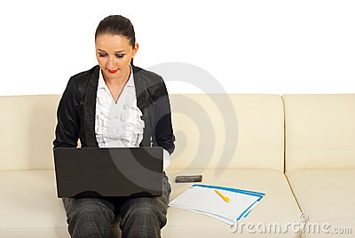 Executive woman using laptop on couch