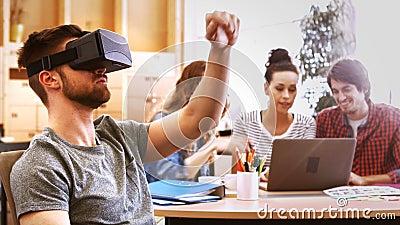 Executivo empresarial masculino que usa auriculares da realidade virtual quando colegas que interagem na mesa vídeos de arquivo
