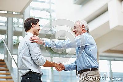 Executivos sênior e novos que agitam as mãos
