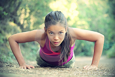 Exercise woman training doing push-ups outside