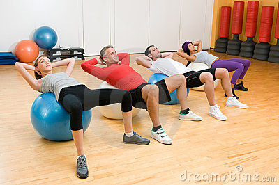 Exercising with fitness ball at gym