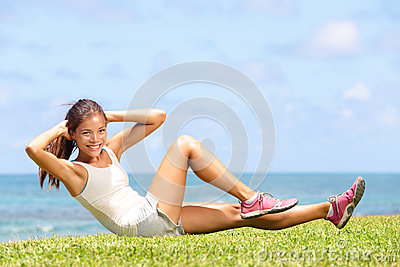 Exercising fitness woman doing sit ups outside