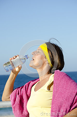 Exercising mature woman drinking water beach
